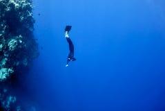 Freediver déménage sous l'eau le long du récif coralien Photographie stock libre de droits