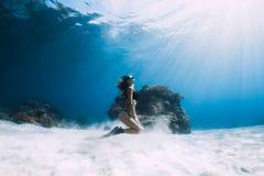Freediver de femme avec des ailerons au-dessus de mer arénacée Eau du fond de Freediving photographie stock
