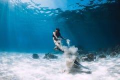 Freediver de femme avec les glissements blancs de sable au-dessus de la mer arénacée avec des ailerons Eau du fond de Freediving photos stock