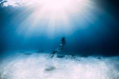 Freediver della donna in bikini sopra il mare sabbioso con le alette Freediving subacqueo fotografia stock