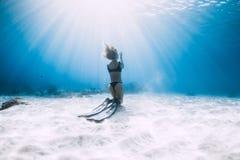 Freediver della donna che posa con le alette sopra il mare sabbioso Freediving subacqueo immagine stock libera da diritti