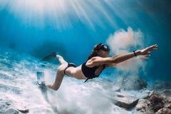 Freediver della donna con la sabbia sopra il mare sabbioso con le alette Freediving in isola hawaiana immagini stock