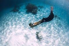 Freediver della donna con la sabbia sopra il mare sabbioso con le alette immagine stock