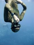 Freediver equalizing pressure while moving down. Meanwhile Blue Hole divers are watching him Royalty Free Stock Images