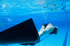 Freediver. Female freediver with monofin swimming underwater in swimming pool Royalty Free Stock Images