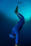 Freediver. Free diver falling into deep darkness along the rope with monofin royalty free stock photos