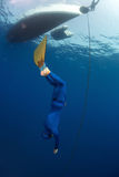 Freediver. Free diver in monofin descending along the metal chain linked to the boat on surface (constant weight discipline stock images