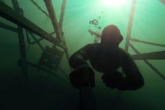 Freediver gående deap i vattnet med en struktur ovanför honom. Arkivbilder