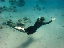 The freediver girl swims along sand sea bottom Stock Photo