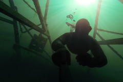 Freediver going deap in the water with a structure above him. Freediver going deap in the water with Sunlight and a metal structure above him Stock Images