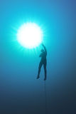 Freediver holding a rope and his breath in the water. Freediver holding a rope and his breath deap in the water with Sunlight above him Royalty Free Stock Images