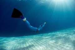 Freediver. Lady free diver swimming in monofin over sandy bottom stock photography