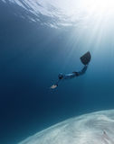 Freediver. Lady free diver swimming over sandy bottom royalty free stock photo