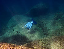 A freediver makes turnover at the sea bottom. The freediver makes turnover at the bottom of the sea near underwater rocks royalty free stock image