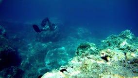 Freediver pływa pod wodą przeciw skale