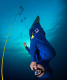 Freediver in the sea. Freediver descending along the rope with monofin. Free immersion discipline Royalty Free Stock Images