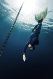 Freediver. Underwater shot of free diver in monofin descending along the metal chain royalty free stock image