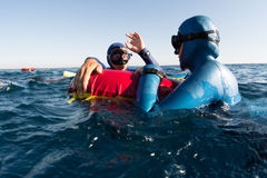 Freedivers. Split shot of two free divers training in sea with buoy Stock Images