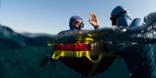 Freedivers. Split shot of two free divers training in sea with buoy Stock Image