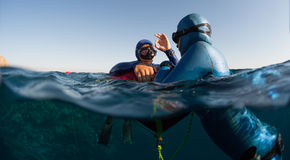 Freedivers. Split shot of two free divers training in sea with buoy Stock Photography