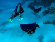 Freedivers swim under the wondering scuba diver. Two freedivers swim under the wondering scuba diver near the bottom of the Red Sea, Dahab, Egypt stock image