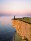 Freedom 1. Young man standing on the cliff with spreaded hands stock images