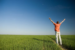Freedom. Young men standing on green grass - arms outstretched Royalty Free Stock Image
