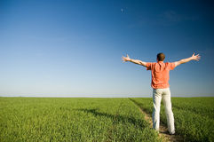 Freedom. Young men standing on green grass - arms outstretched Royalty Free Stock Images
