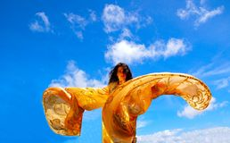 Freedom. A beautiful Caucasian dancing woman with golden moving shawl wings in front of blue sky background Royalty Free Stock Image