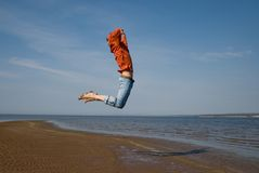 Freedom. Young man highly jumps on coast Royalty Free Stock Images
