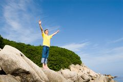 Freedom. The man costs(stands) on rocks having stretched hands Royalty Free Stock Photo