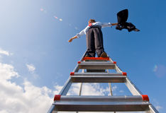 Freedom. A businessman spreading his arms in the wind, standing on top of a ladder, whilst holding his jacket Stock Image