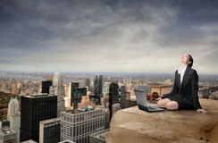 Freedom. Smiling businesswoman sitting on the top of a skyscraper with a laptop in front of her Stock Photos