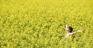 Freedom. Young beautiful girl enjoying a sunny day on canola field Stock Images