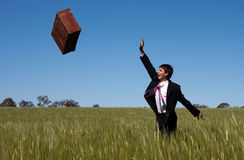 Freedom. Businessman letting go and release past baggage and instantly enjoys the freedom against a blue sky green grass landscape Stock Images