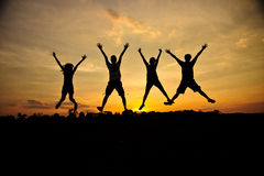 Freedom. Silhouette of friends jumping in sunset Royalty Free Stock Image