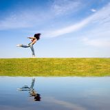Freedom. Woman jumping on green field, with water reflection Royalty Free Stock Image