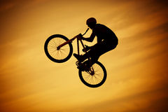 Freedom. Bmx jump on bright orange sky background Royalty Free Stock Photos