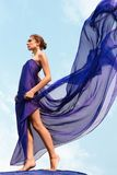 Freedom. Photo of graceful female folded in dark blue chiffon shawl with cloudy sky at background Stock Photo