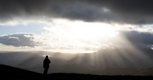 Freedom. Hiker looking at scenic view as sun bursts through clouds, Lake District, England Royalty Free Stock Image