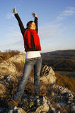 Freedom. Young girl stretching her arms on top of a mountain feeling freedom Royalty Free Stock Image