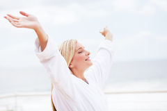 Freedom. Concept: cute young woman in bathrobe with her arms opened in the morning Stock Photo