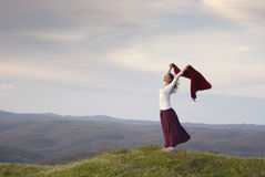 Freedom. Beautiful young woman standing on top of mountain feeling empowered expressing joy and freedom Stock Photography