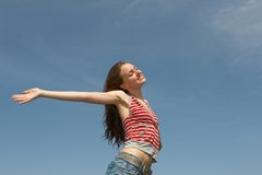 Freedom. Pretty young girl on a background of the blue sky Royalty Free Stock Photo