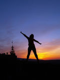 Freedom. Silhouette of a young woman embrace the the rays of the sunset sun over an old village Stock Photos
