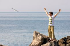 Freedom. Happy young man standing on top of mountain with ocean on background Royalty Free Stock Image