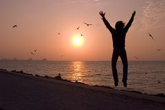 Freedom. Picture of a man jumping at the beach during sunrise Royalty Free Stock Image