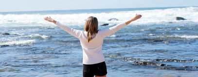 Freedom. A young caucasian girl standing at the beach expressing joy of life with her arms open Stock Images