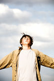 Freedom. Teen portrait, standing in the wind and reaching arms out against cloudy sky background stock image