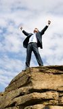 Freedom. Happy businessman standing on the top of mount with his arms raised to the sky stock photo